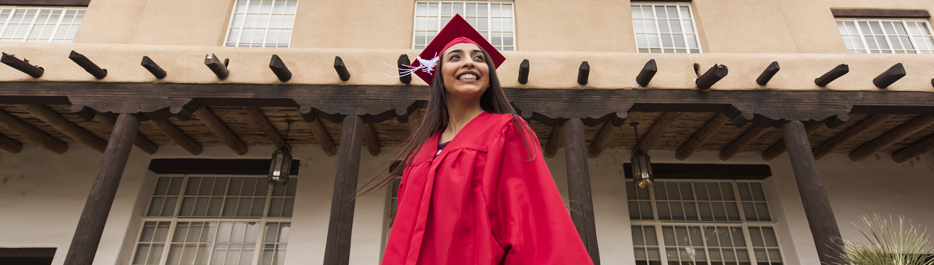 photo of graduating student in front of Zimmerman Library
